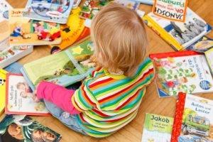 Kind ist von Kinderbüchern umringt