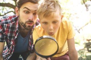 Vater und Sohn schauen in eine Lupe