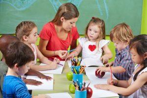 Kinder sitzen mit einer Erzieherin am Tisch