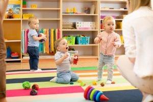 kleine kinder mit spielzeug in kindergarten