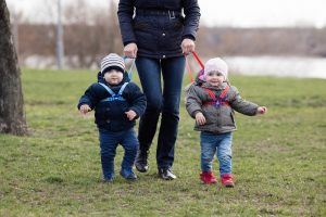 Mutter hat ihre Zwillingen an einer Leine