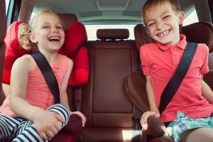 Kinder sitzen auf Sitzerhöhungen im Auto