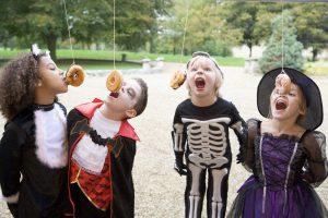 Kinder versuchen an Schnüren hängende Donuts zu essen