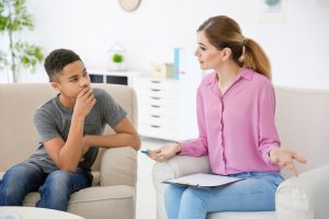 ein Junge hört seiner Therapeutin zu