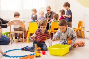 Kinder spielen im Kindergarten mit Erzieherin im Hintergrund