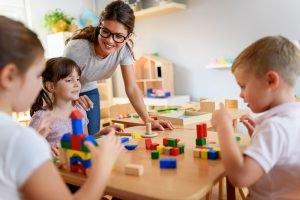 Erzieherin spielt mit Kindern in der Kita