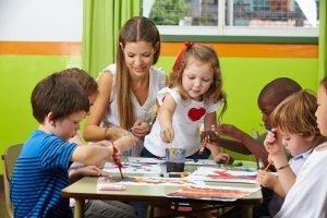Kinder malen zusammen mit Erzieherin