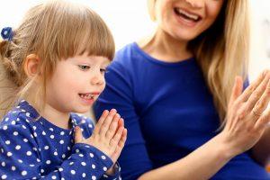 Mutter spielt mit ihrer Tochter Klatschspiele