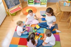Erzieherin sitzt mit einer kleinen Gruppe von Kindern im Kreis