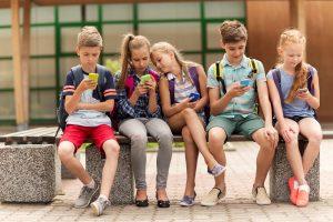 mehrere kinder sitzen mit einem smartphone in der hand nebeneinander