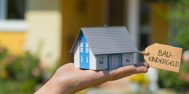 Hand balanciert kleines Haus mit banner Baukindergeld