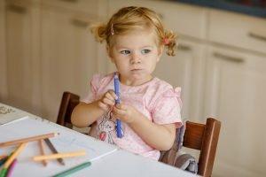 ein kleines maedchen sitzt mit einem stift in der hand an einem tisch