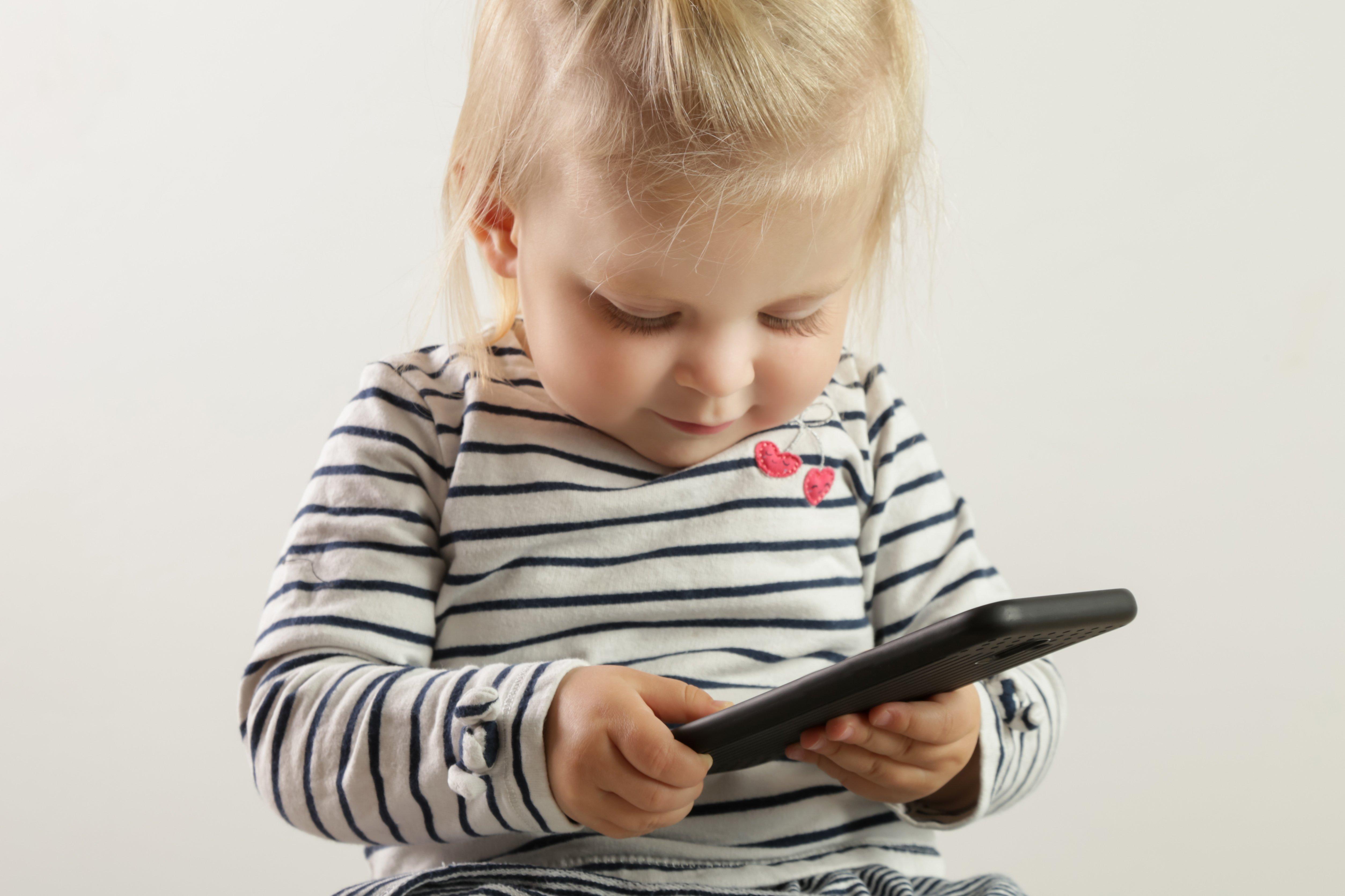 kleines mädchen spielt am smartphone