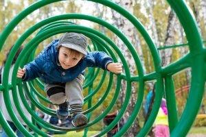 Kind klettert auf dem Spielplatz