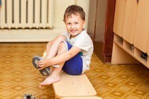 Kind zieht seine Klettverschluss-Schuhe an