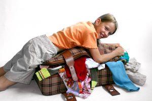 ein kind versucht einen ueberfuellten koffer zuzumachen