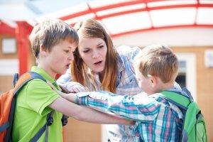 Handgreiflichkeiten zwischen zwei Schülern, die von einer Lehrerin gestoppt werden