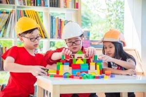 drei Kinder bauen gemeinsam mit Bauklötzen