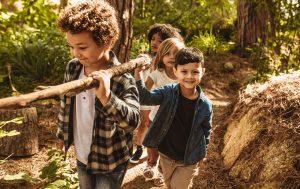 Kinder tragen einen Baumstamm