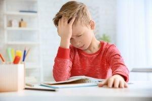 Junge kann sich aufgrund von Kopfschmerzen nicht konzentrieren