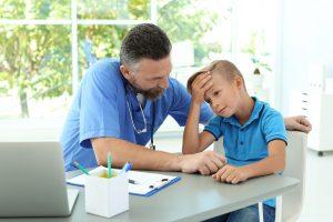 Junge mit Kopfschmerzen beim Arzt