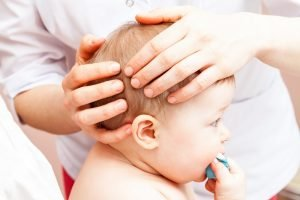 aerztin tastet an einem babykopf