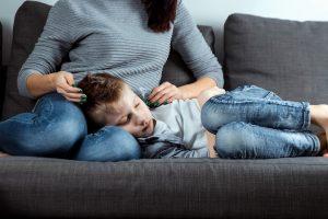 krankes Kind liegt auf dem Schoß der Mutter