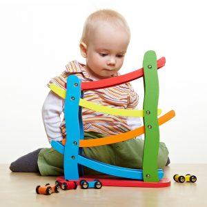 Kleines Kind spielt mit Autos und einer Kugelbahn