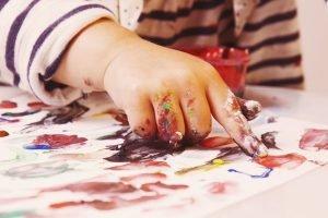Kind malt mit den Händen
