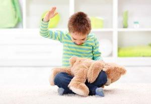 Ein Junge schlägt seinen Teddybär