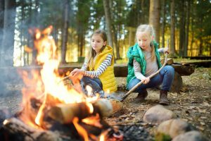 zwei maedchen sitzen zusammen am lagerfeuer