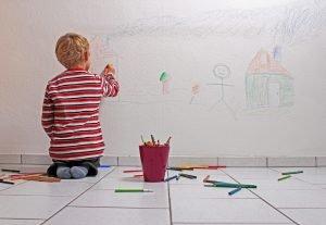 Kind bemalt die Wand