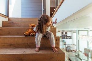 Kleines Mädchen sitzt im Treppenhaus