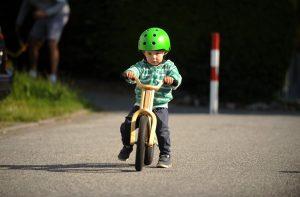 Kind fährt mit einem Laufrad aus Holz