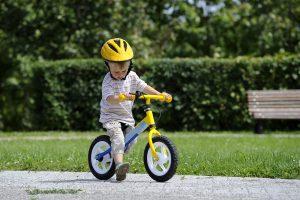 Junge fährt auf einem Laufrad mit Stange