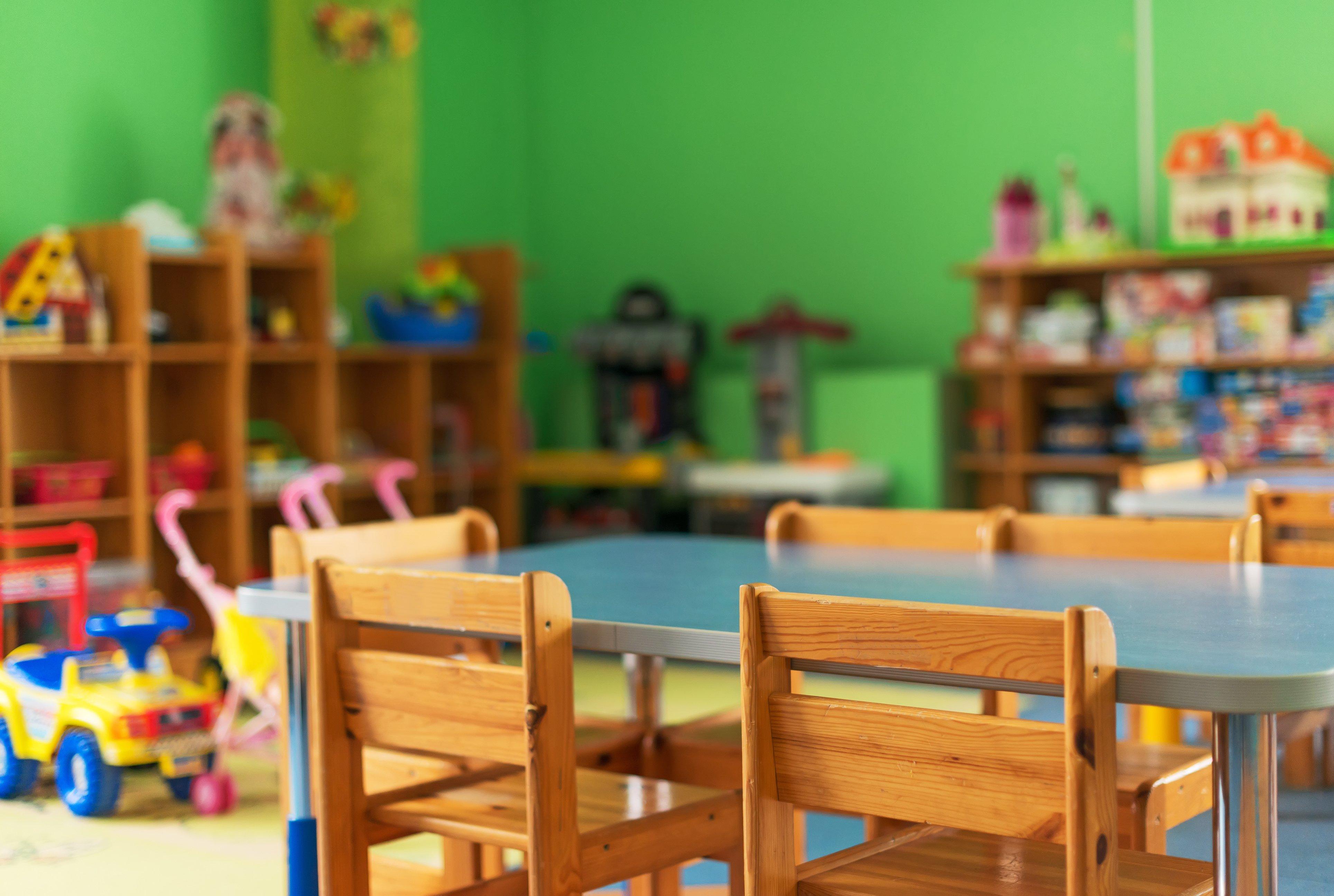 Raum mit Spielsachen, Tisch und Stühlen einer Kita ohne Kinder