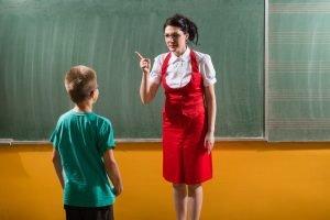 Lehrerin steht mit erhobenem Zeigefinger vor einem Schüler