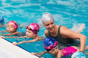 grundschullehrerin hilft kindern beim schwimmunterricht