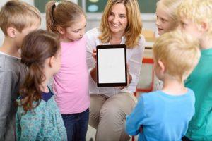 eine lehrerin zeigt kindern in der grundschule ein tablet