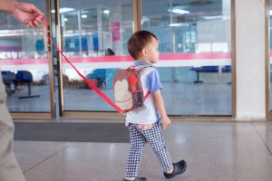 Kind mit einer Leine am Rucksack