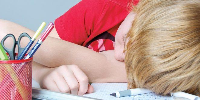 Kind liegt niedergeschlafen den Kopf neben die Schulaufgaben