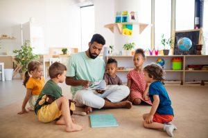 erzieher liest kindern etwas vor