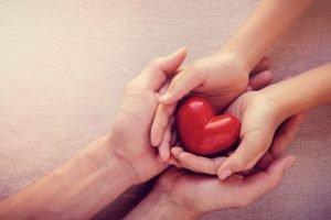 Kind und Erwachsener halten gemeinsam ein Herz