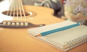 ein notizbuch sowie ein stift liegen auf einer gitarre