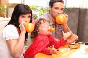 Familie pustet gemeinsam Luftballons auf