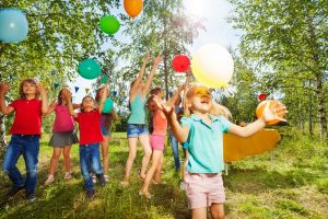 kinder spielen bei einem gruppenspiel draußen mit luftballons