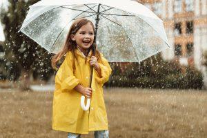 Mädchen mit Regenjacke und Regenschirm