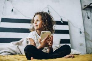 ein kleines maedchen sitzt mit einem smartphone auf dem bett