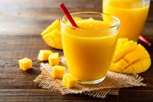 ein mango-smoothie in einem glas mit einer frischen mango auf einem holztisch