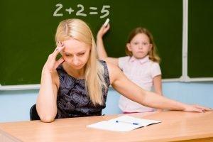 verzweifelte Lehrerin mit einem Kind, dass unfähig ist, eine Matheaufgabe zu lösen